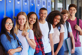 students smiling and standing near blue lockers